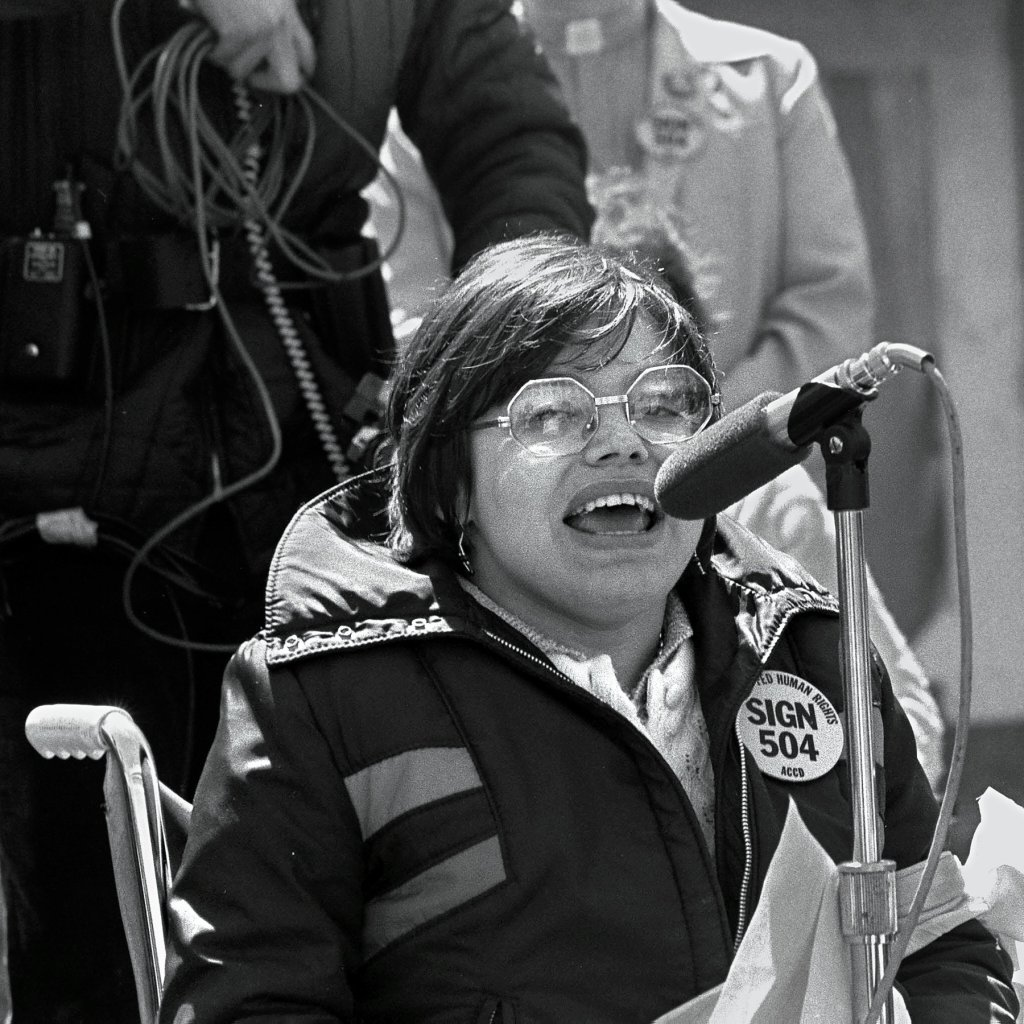 """Black and white photo of Judy at the 504 protests in the 70s.  Judy Heumann, a cis-gender white woman who is a wheelchair user with short brown hair. She is wearing glasses and a jacket with a 504 pin that says """"Sign 504 Now"""" She is passionately speaking at a microphone."""