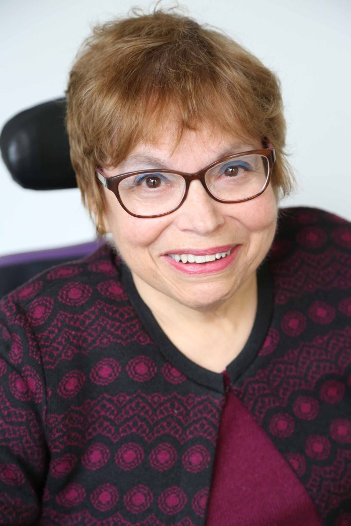A headshot of Judy Heumann, a cis-gender white woman who is a wheelchair user with short brown hair. She is wearing red glasses and a maroon and black embroidered sweater with the top buttoned with a matching maroon shirt underneath. She is smiling kindly.